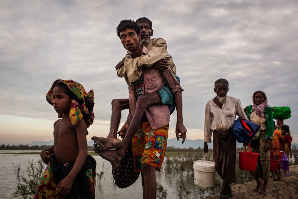 Mohammed H., 23, carries his father Abdu S., 60, blind and unable to walk since fleeing their village in Buthidaung Township. Stranded in Myanmar on the banks of the Naf River for one month, they left behind three surviving family members suffering from illness. Patrick Brown © Panos/UNICEF 2018