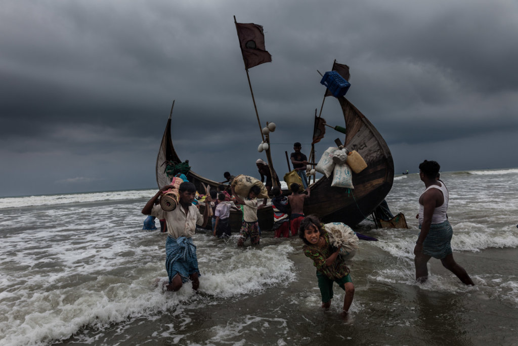 Noor Haba, 11, carries her family's belongings to Shamlapur Beach in Bangladesh after the boat she traveled on from Maungdaw Township, Myanmar arrived safely at 8:43 a.m. Patrick Brown © Panos/UNICEF 2018