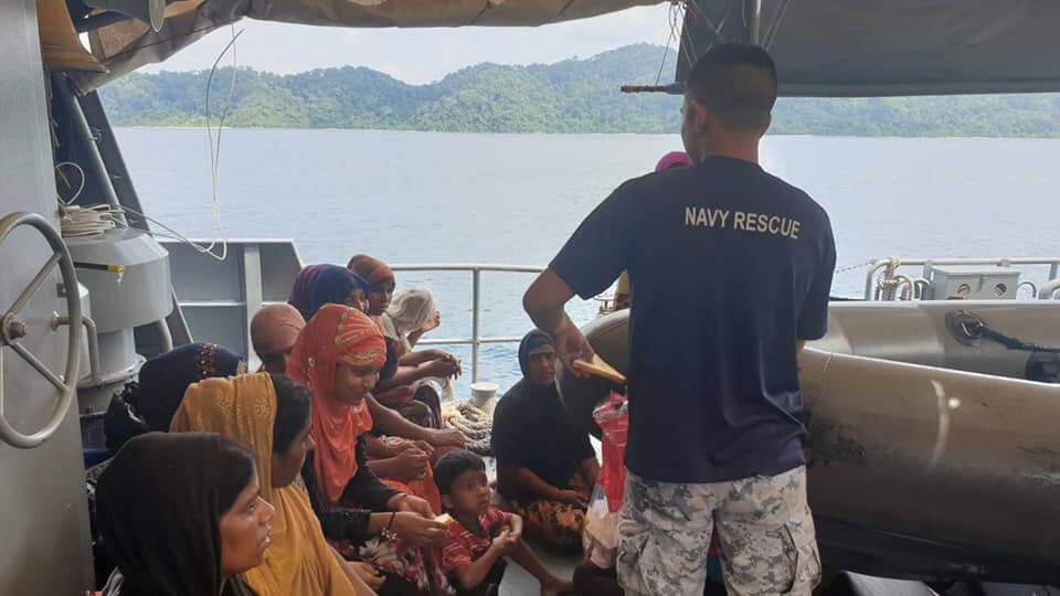 Thai Navy official giving bread to Rohingya refugee women who recently arrived to Thailand by boat. ©Wassana Nanuam, 2019