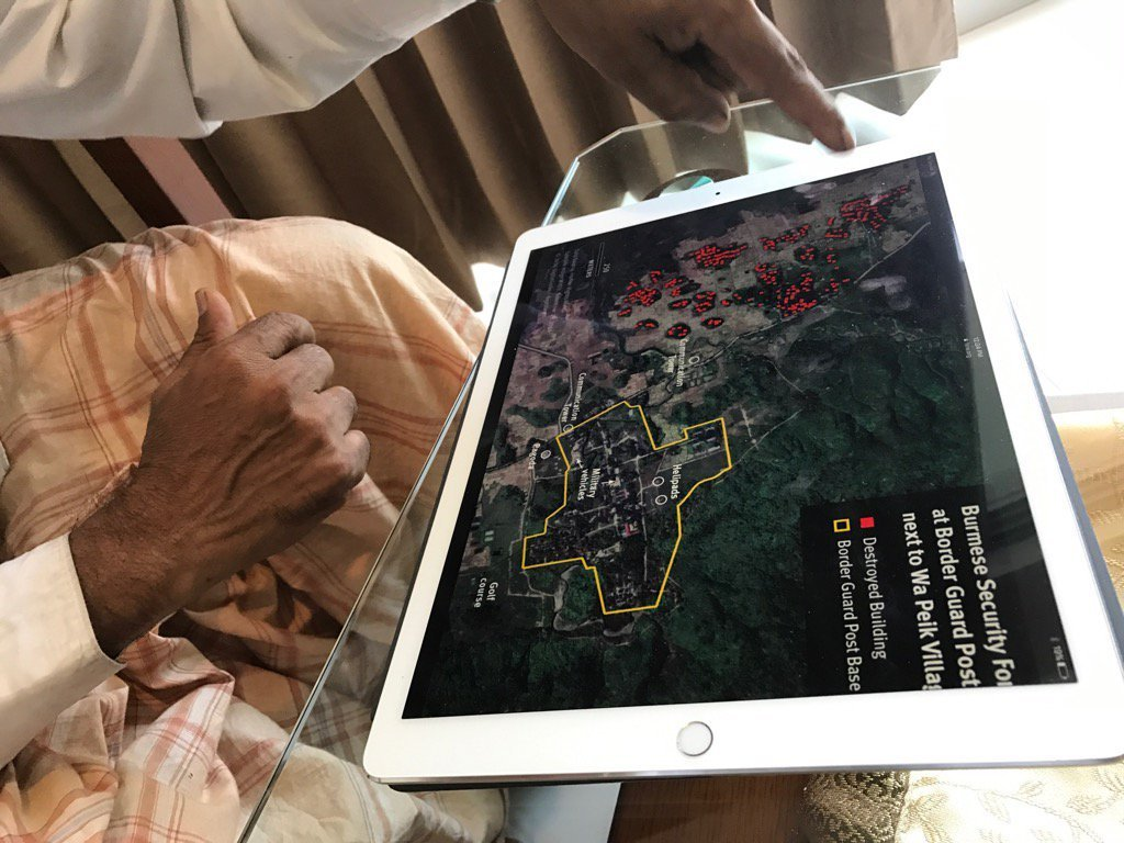 Rohingya survivor uses Human Rights Watch satellite imagery to explain to Fortify Rights how Myanmar Army soldiers burned down Wa Peik Village. ©Fortify Rights, 2016