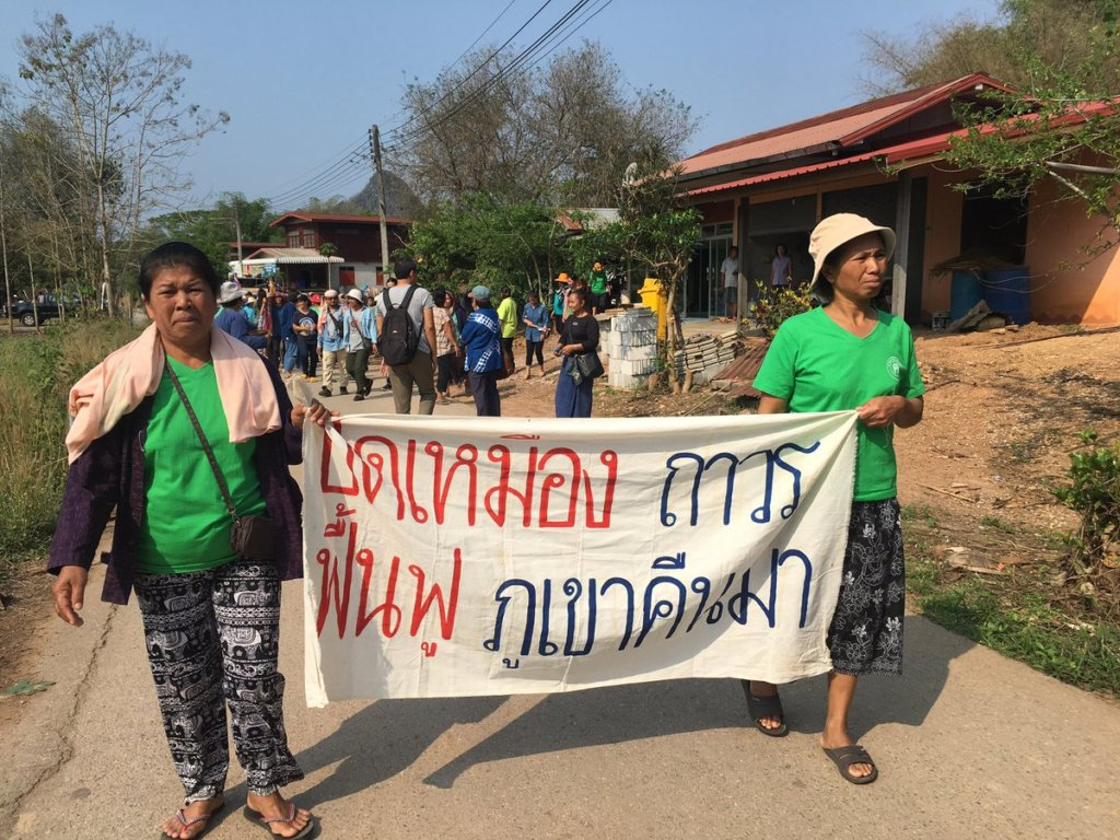"Khon Rak Ban Kerd Group march to raise awareness and support for environmental protections in Loei Province. Women leaders hold a sign that reads, ""Close the Mine Permanently, Rehabilitate and Bring Back Our Mountains."" ©Fortify Rights 2017"