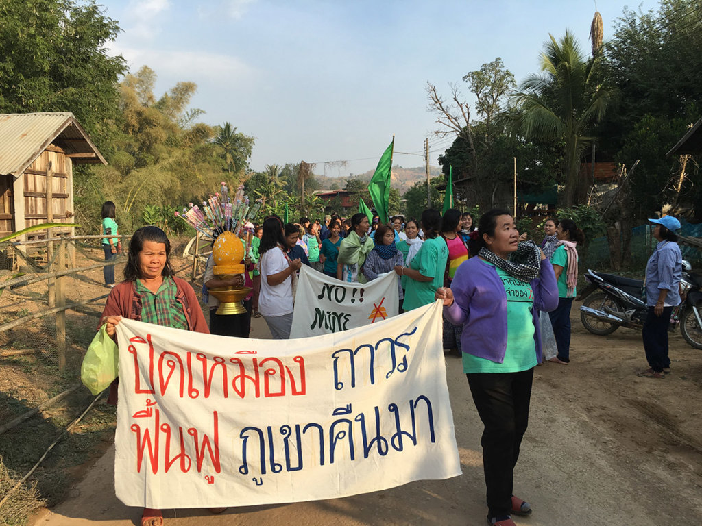 """Khon Rak Ban Kerd Group march to raise awareness and support for environmental protections in Loei Province. Women leaders hold a sign that reads, """"Close the Mine Permanently, Rehabilitate and Bring Back Our Mountains."""" ©Fortify Rights 2016"""