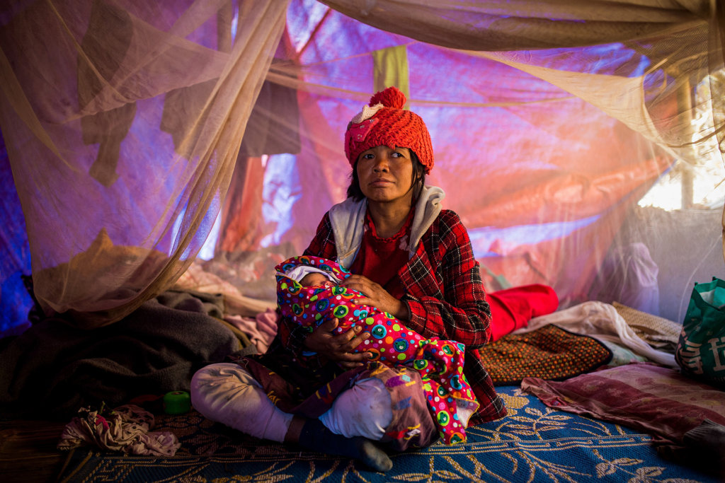 A displaced Kachin woman rests at a temporary shelter with her week-old infant in Lungbyang village, Waingmaw Township, Kachin State. The child was born while his mother fled from Zai Aung camp for displaced persons after the Myanmar Army fired a mortar near their camp. Displaced mothers and children are disproportionately affected by government-imposed deprivations in aid and healthcare. ©Hkun Lat, January 2017.