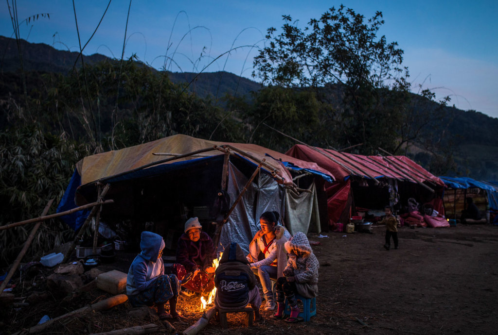 A displaced Kachin family keeps warm around a fire in front of their temporary shelter near Lungbyang village, Waingmaw Township, Kachin State. Displaced Kachin struggle to find essential non-food items, such as firewood, in displacement camps in Kachin State, where winters can be harsh. ©Hkun Lat, January 2017.