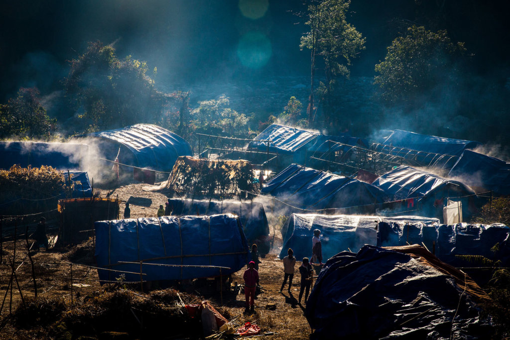 Displaced Kachin warm themselves in the morning sun in front of their temporary shelter near Lungbyang village, Waingmaw Township, Kachin State. As a result of the Myanmar military's restrictions on humanitarian aid, shelters for the displaced in Kachin State are often inadequate and in disrepair. ©Hkun Lat, January 2017.