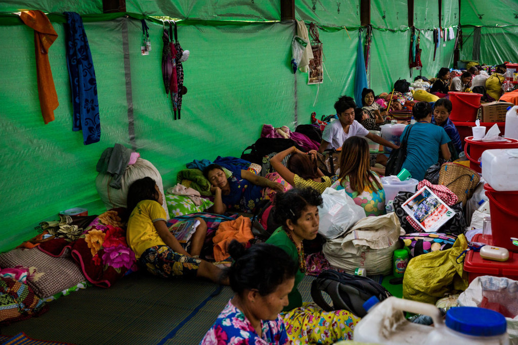 Forcibly displaced Kachin huddle in a temporary shelter at Jaw Masat camp in Myitkyina Township, Kachin State. Displaced civilians fled here after being forced from their homes by fighting between the Myanmar military and the Kachin Independence Army. The Myanmar military denied aid groups access to them in April and May 2018. ©Hkun Lat, May 2018.