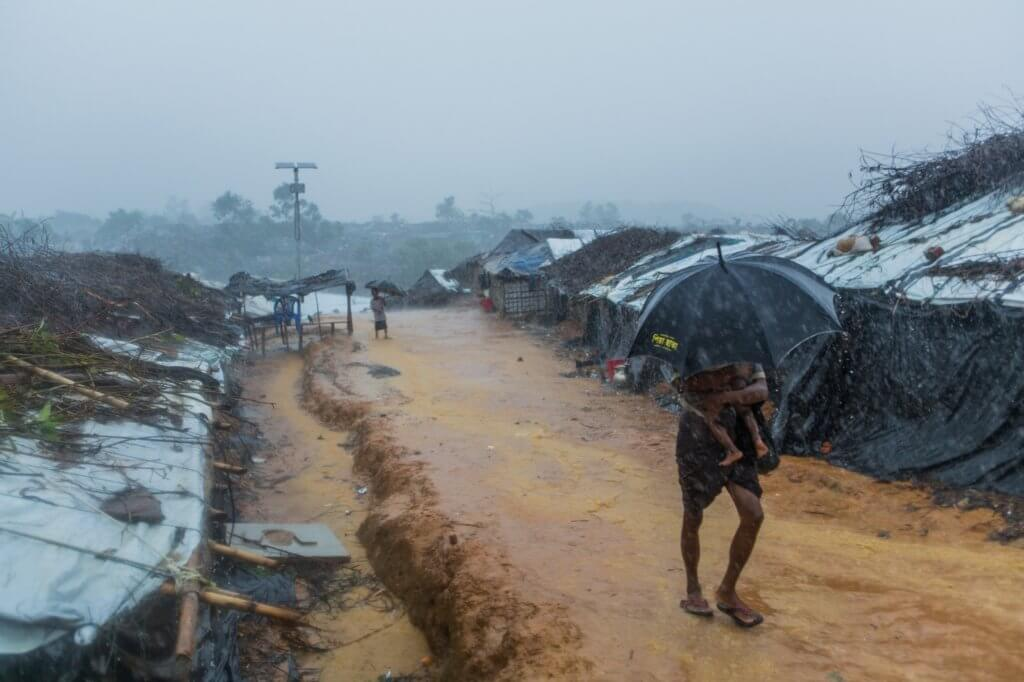 Rohingya refugee man with child walks through monsoon rain in Kutupalong refugee camp, Cox's Bazar District, Bangladesh. ©Reza Shahriar Rahman, 2016