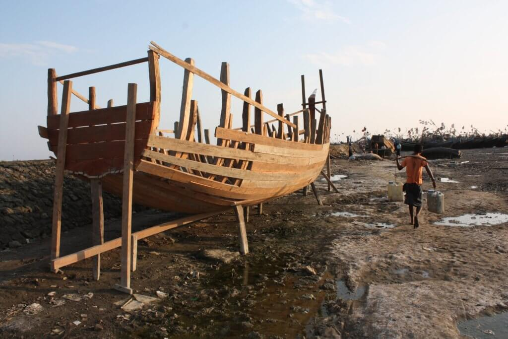 A boat under construction on the coast of Rakhine State, Myanmar. Residents told Fortify Rights the boat would transport Rohingya to larger ships in international waters operated by human traffickers. ©Fortify Rights, 2015