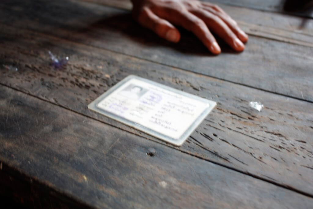 """A Rohingya man confined to an internment camp in Myanmar's Rakhine State displays his """"white card""""—an identification document revoked by former Myanmar President Thein Sein. Myanmar stripped Rohingya of equal access to citizenship rights in 1982, heightening the risk of being trafficked for Rohingya. ©Fortify Rights, 2015"""