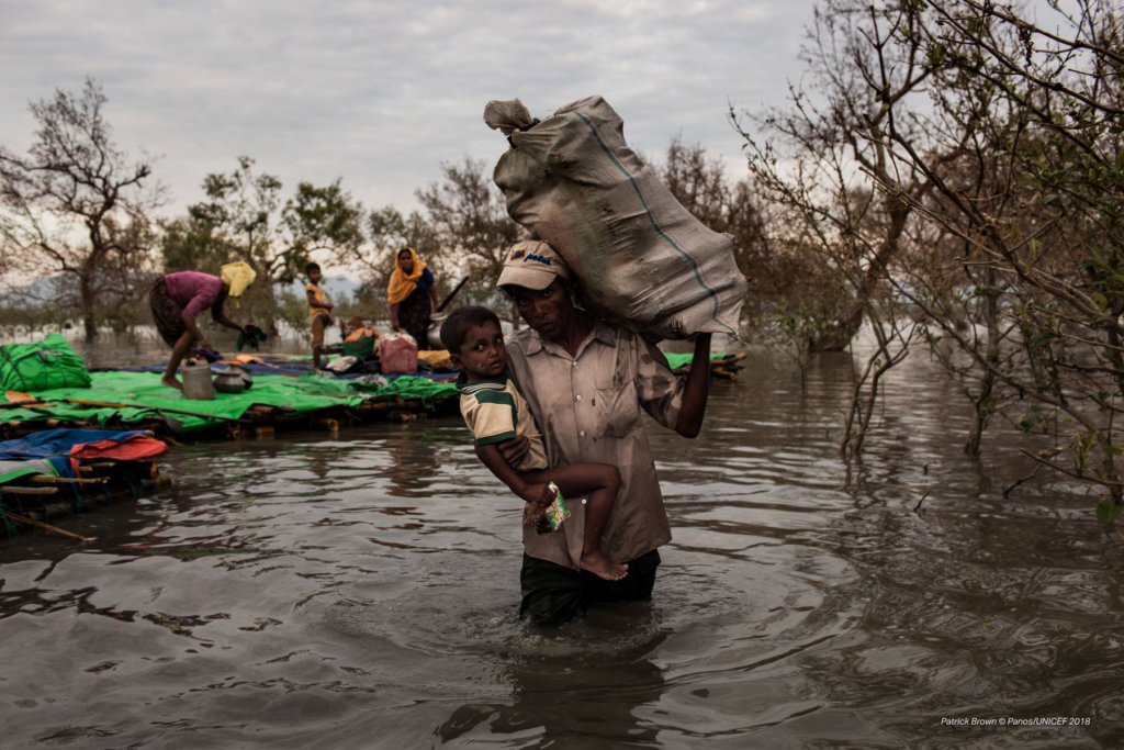 Stranded on the Myanmar border for up to three weeks, Rohingya refugees cross the Naf River into Bangladesh—a five to seven-hour-long journey—on makeshift rafts made of bamboo, tarp, and empty palm-oil cans. Patrick Brown © Panos/UNICEF 2018