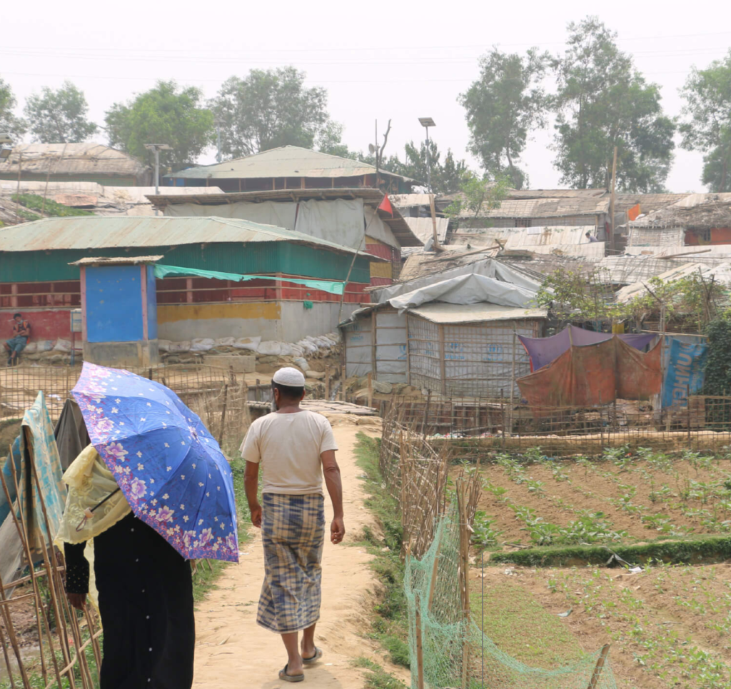 A Rohingya man and woman walk through a refugee camp in Cox's Bazar District, Bangladesh. ©Fortify Rights 2020