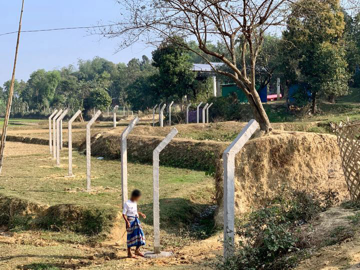 A Rohingya man walks near the construction of a perimeter fence around Kutupalong refugee camp, Cox's Bazar District, Bangladesh. ©Fortify Rights 2020