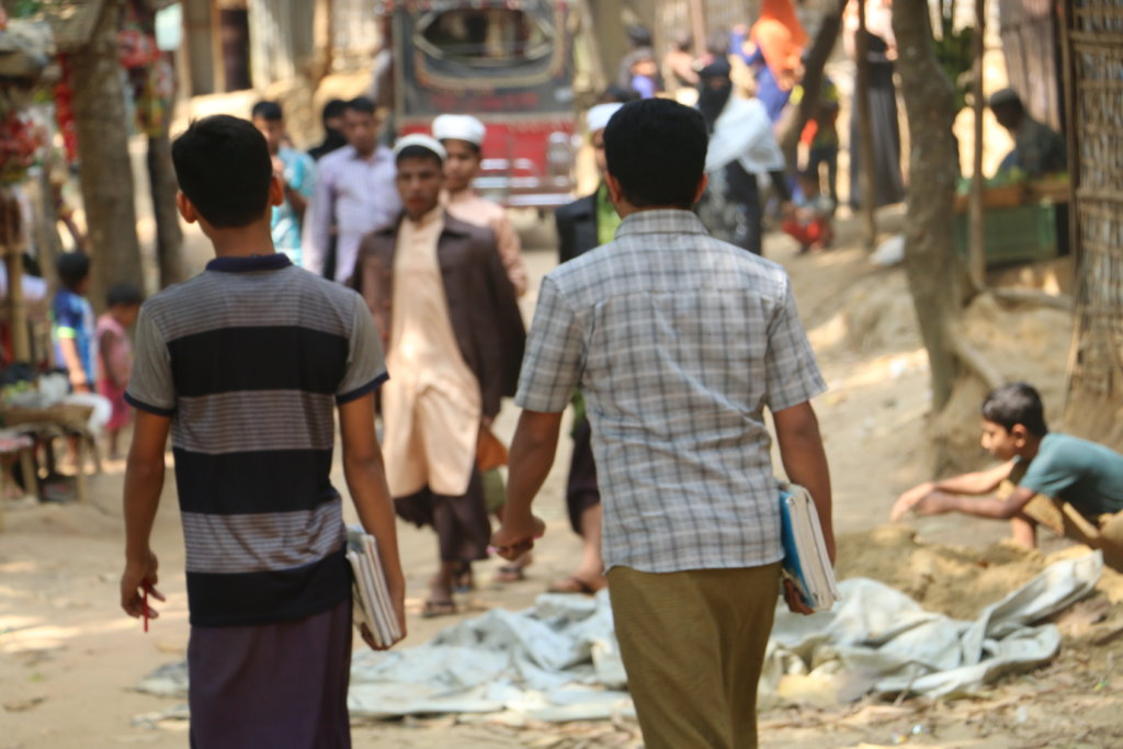 Two Rohingya men walk through Kutupalong junction in Cox's Bazar District, Bangladesh. The Rohingya refugees live in 34 refugee camps in southern Bangladesh. The Kutupalong-Balukhali Expansion Camp is the largest refugee camp. ©Fortify Rights 2020