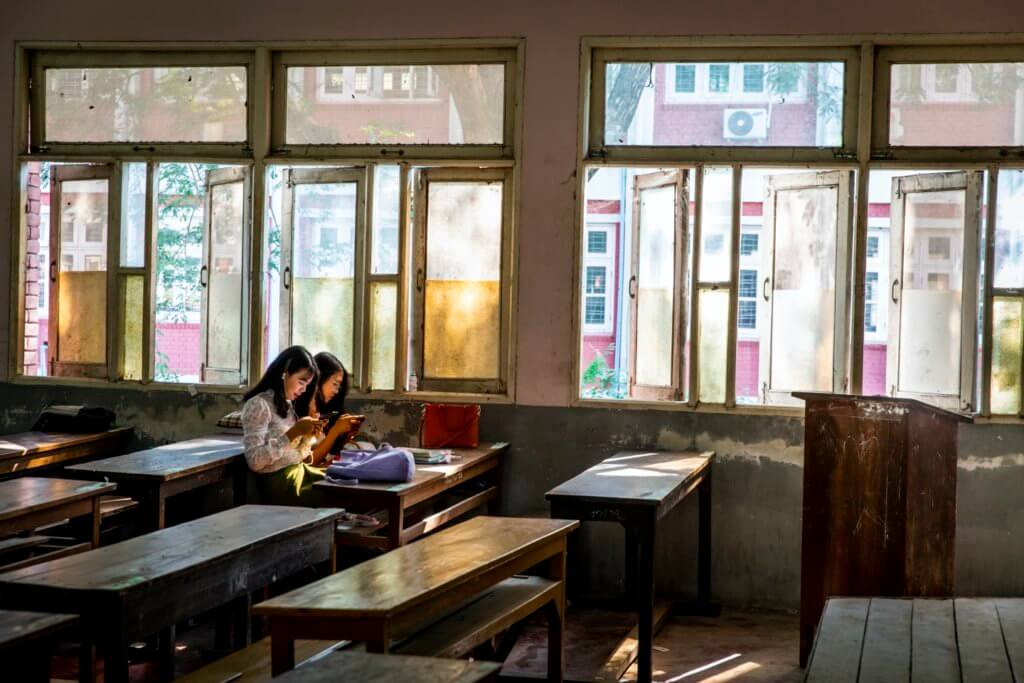 Two Yadanabon University students sitting in a classroom. The students' protests argued that the university should invest more resources into classroom needs, such as chairs and study materials. ©Hkun Lat, January 2020