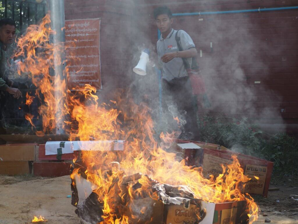 Kyaw Thiha Ye Kyaw stands beside a burning mock-coffin at a peaceful protest at Yadanabon University, December 28, 2018. ©Myanmar Pressphoto Agency